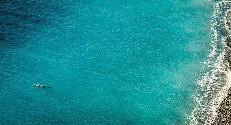 A woman swimming in a dark green-blue sea.