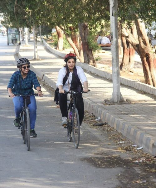 Two women cycling together on a derted street lined with trees
