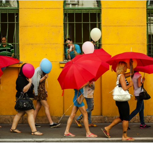 A group of women walking holding red umbrellas that cover their faces.