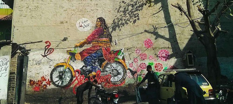 Wall graffiti showing a plus-sized woman dressed in a lehenga on a motorbike