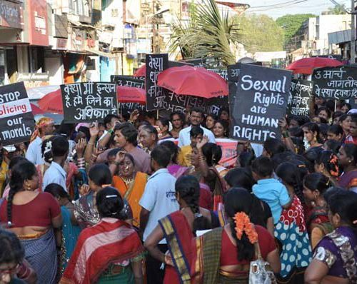 """A protest by sex workers. They are wearing sarees, holding red umbrellas, and placards reading """"Stop policing our morals"""", """"Sexual rights are human rights""""."""