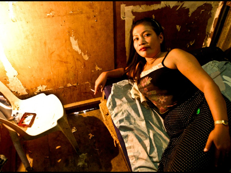 A sex worker lying on her side on a bed in a run-down room, smoking.