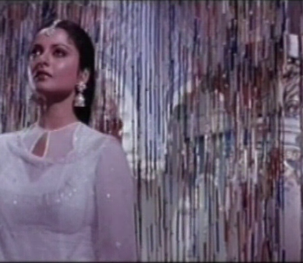 Still from a Bollywood song. A woman in white dress.