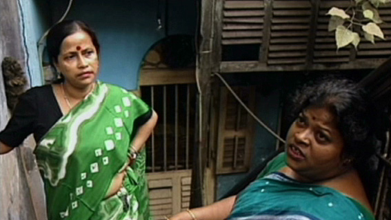 Two sex workers standing and talking outside a chawl. They both are dressed in sarees, and are wearing a red bindi on their forehead.
