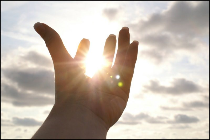 Photo of a hand in front of a cloudy and sunny sky. The picture is clicked such that it seems the sun is held in the palm of the hand.