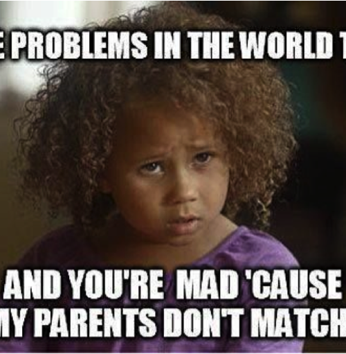 """A brunette child with curly hair looks in anger. Over the photo written in bold and caps in white colour, """"All the problems in the world today, and you're mad 'cause my parents don't match?"""""""