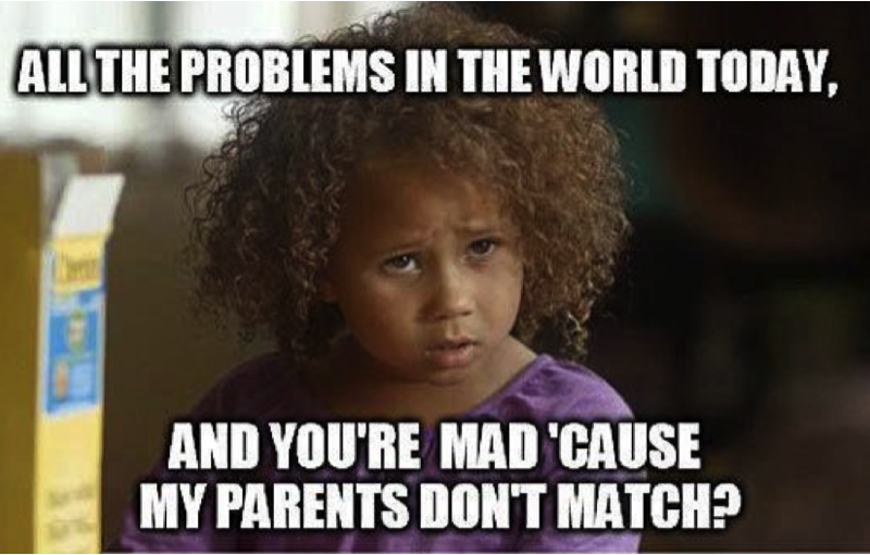 "A brunette child with curly hair looks in anger. Over the photo written in bold and caps in white colour, ""All the problems in the world today, and you're mad 'cause my parents don't match?"""