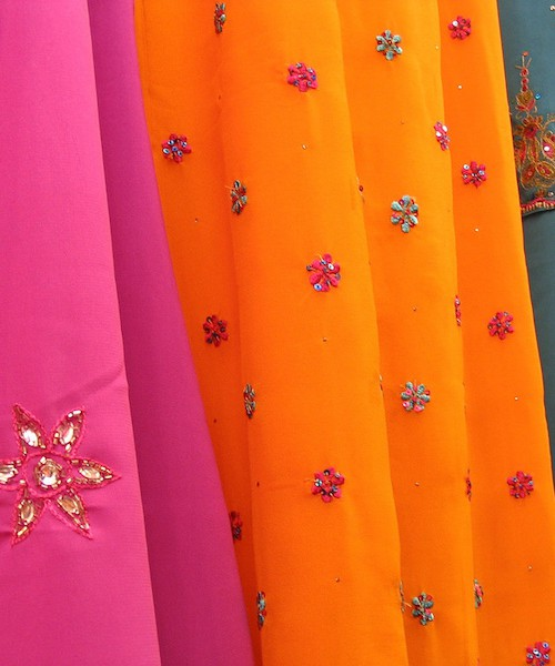 Photo of Indian dresses. A pink saree, an orange saree, and a blue salvar suit - all three have colourful flowers and designs on them. Screen reader support enabled. Photo of Indian dresses. A pink saree, an orange saree, and a blue salvar suit - all three have colourful flowers and designs on them.