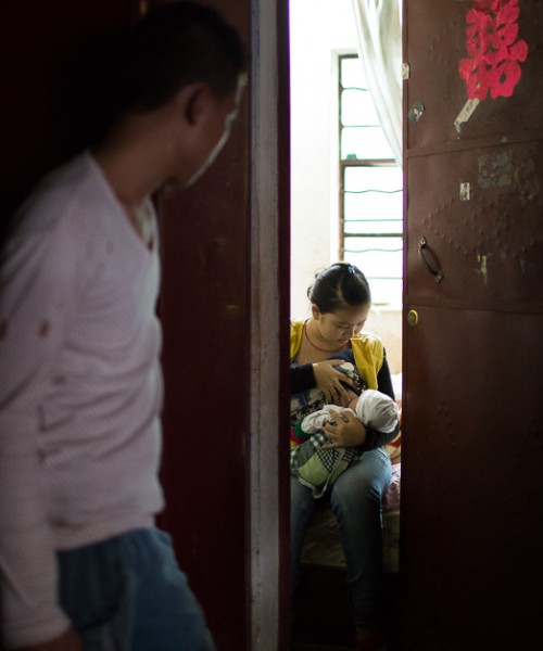 A boy looking in a room through a creaked door. There, a girl is breastfeeding a baby.
