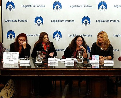 "Six women behind a table giving a press conference. To the left stands the Aragentinian flag. Behind them is a white cloth on which is printed ""legislatura portena"" with a symbol or logo of Buenos Aires City Legislature in blue colour. The words and the photo are printed all over the cloth in a line."