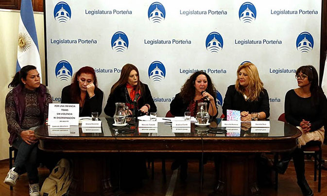 """Six women behind a table giving a press conference. To the left stands the Aragentinian flag. Behind them is a white cloth on which is printed """"legislatura portena"""" with a symbol or logo of Buenos Aires City Legislature in blue colour. The words and the photo are printed all over the cloth in a line."""