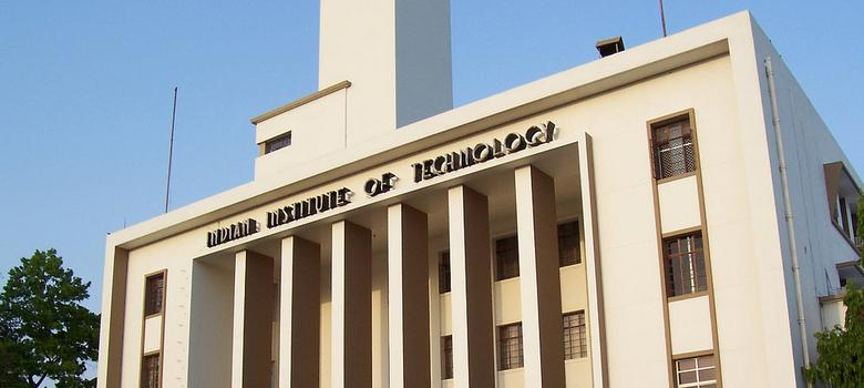 """Photo of a front of a light yellow-painted college building. At the top of the building are the words, """"Indian Institute of Technology""""."""