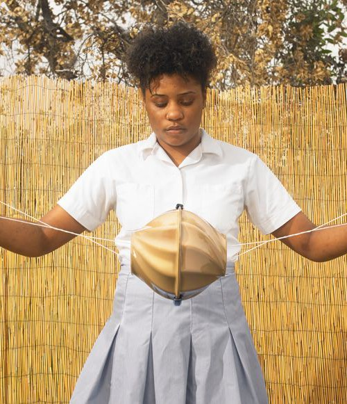 A brown girl is holding the Flo toolkit that supports girls living in poverty to wash, dry and carry reusable sanitary pads. It has a ball-type shape in the middle, and a string on both ends. The girl is stretching the string as if to give the central part a spin.