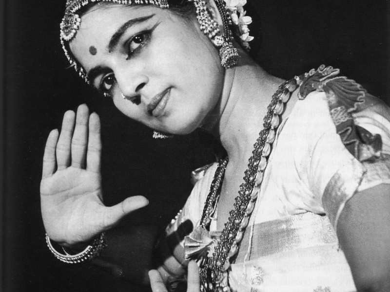 Black-and-white photo of Indian bharatnatyma dancer Rukmini Devi holding a mudra. She is wearing traditional dance clothing with flowers in her head, and jewellery on the forehead, ears, and neck. The image is from the chest up.