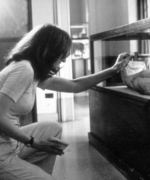 A black-and-white photo of a woman in jeans and tee-shirt bent down to clean a glass vitrine in a museum.
