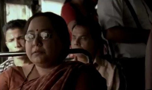 Screenshot from a video. A middle-aged Indian woman sitting in a crowded bus. She is wearing orange saree, red bindi, and specks.