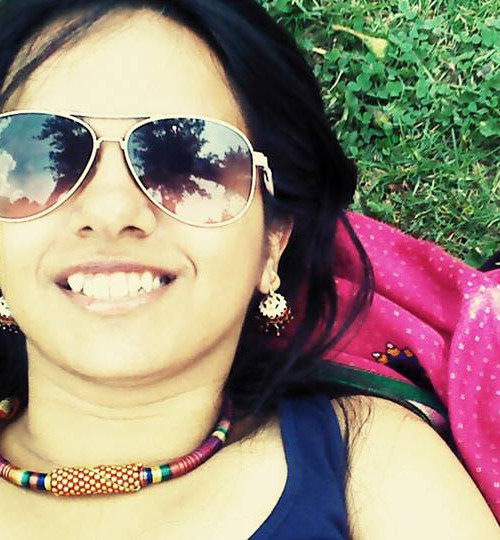 Feminism in India founder Japleen Pasricha lying under the sun on grass. She is smiling, wearing goggles, earrings, necklace, and a tank top.