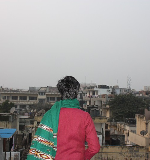 Back of a woman with boy-cut hair, wearing red sweater, and a green shawl round her neck, looking at the view from a terrace. She can see houses and more houses.