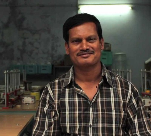Arunachalam Muruganantham smiling at the camera. He has a moustache, and wearing a checked black and white shirt.