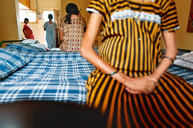 A malnourished pregnant woman sitting on a hospital bed. She is wearing a striped yellow and black gown. Screen reader support enabled. A malnourished pregnant woman sitting on a hospital bed. She is wearing a striped yellow and black gown.