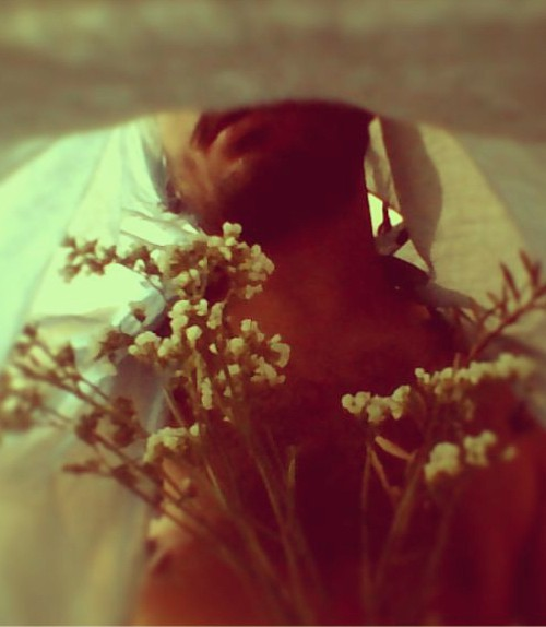A nude man with a bedsheet over his head, is holding a bunch of small white flowers. The photo is clicked from inside the bedsheet. He is visible from the lips till the midrif.