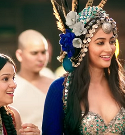 Pooja Hegde in film 'Mohenjo Daro' wearing a big headdres with white and blue roses, and feathers popping out of it.