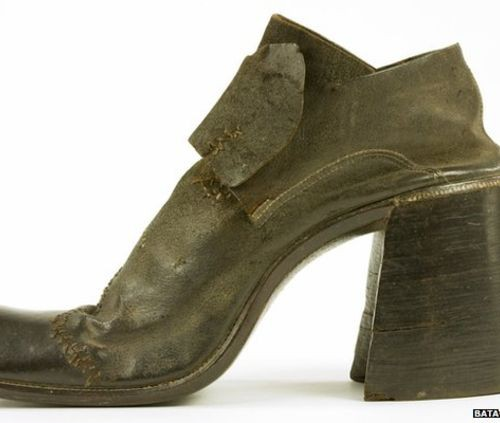 "A brown leather shoe with thick, high heels. On the bottom right corner is written ""BATA shoe museum""."