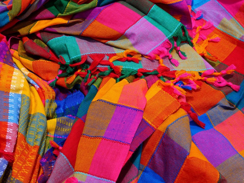 Bright, goddy-coloured shawls lying in a messy, scattered way. Screen reader support enabled. Bright, goddy-coloured shawls lying in a messy, scattered way.