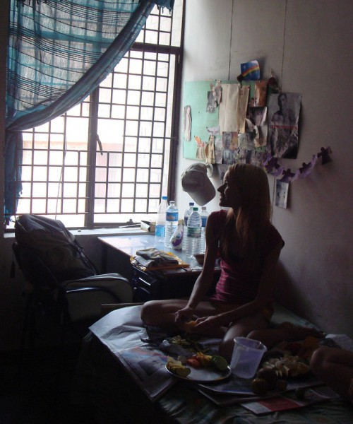 A woman sitting on a bed in her room wearing shorts and a tank top, looking out the window.
