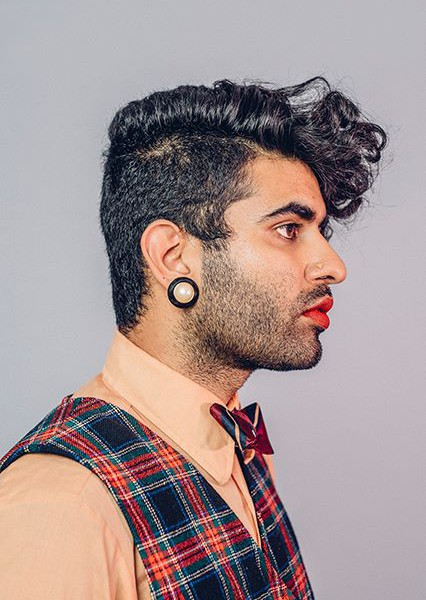 """A right profile of Alok Vaid-Menon with a stub, wearing red lipstick, yellow nosering, big golden and black earrings, and hair parted by the side - with right side """"manly"""" hair, and left - longer and curlier."""