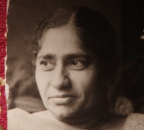 A vantage photo of an Indian woman wearing suit and chunni. We can see the face and shoulders.