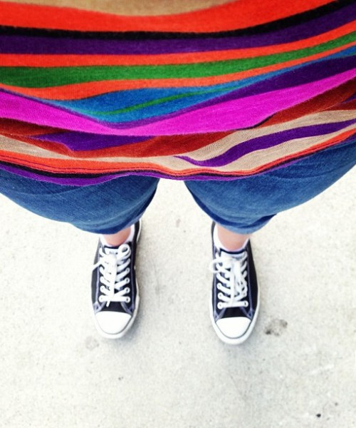Selfie by a woman showing her striped, bright-coloured top, blue capri, and black and white sneakers.