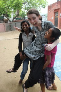 "Image of a White woman with a small ponytail in ""Indian dress code"", wearing 'salwar-kameez' and being, to her surprise, lifted up by two grinning girl children."