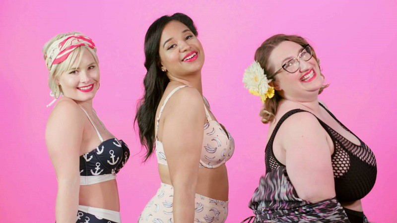 Three women of different sizes who could be called healthy and fat, each wearing a bikini, and smiling proudly at the camera.