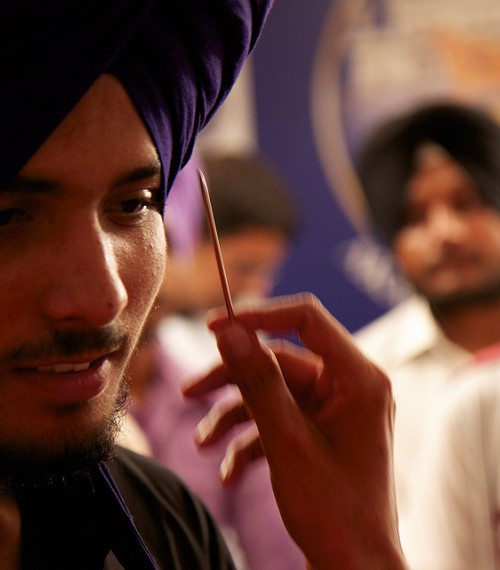 A close-up of the face of sikh man in a purple turban or dastar. Another person's hand pointing at his truban with a toothpick. Behind him are two other men in turban who are blurred out.