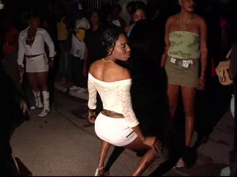 A black woman in a white shoulder top and white shorts dancing unfazed. She is the dancing pose where she is a little bent with her knees to the side and outward.