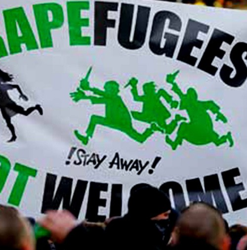 """A photo of a protest with a focus on a placard that says in bold and all caps, """"Rapefugess not welcome"""" with words """"rape"""" and """"not"""" in green, and the rest in black. In the middle is drawn a woman running away from a three men who are holding daggers in their hands, running towards her."""