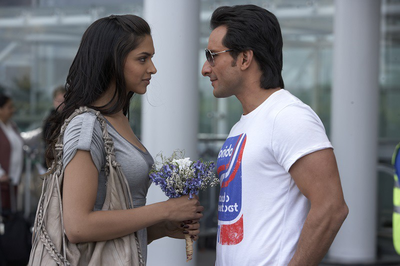 Still from a film 'Love aaj kal'. A man and a woman in their 20s at an airport facing and looking at each other. The woman is holding a small bouquet of purple and white flowers.