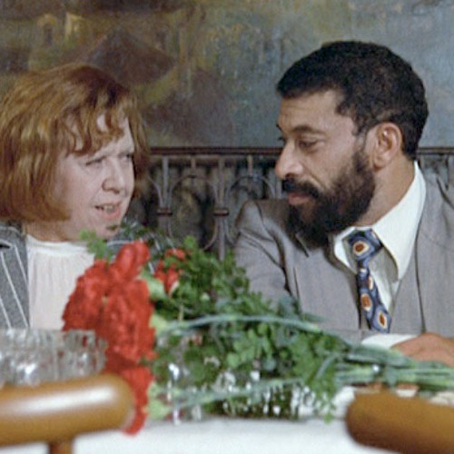 Still from a film. A man and a woman at a restaurant table, talking. A bunch of red flowers are kept on the table in front of them.