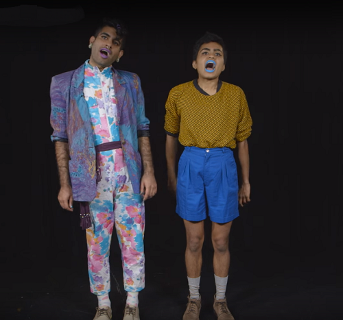 Photo of two brown, queer boys on a stage performing in front of a dark black background. One is wearing earrings, a blue overcoat, and a wite jumpsuit which has big baby pink and baby blue-colours flowers. Another is wearing bright blue lipstick, orange tee, and blue kneww-length shorts. They have their mouths wide open as if singing something.
