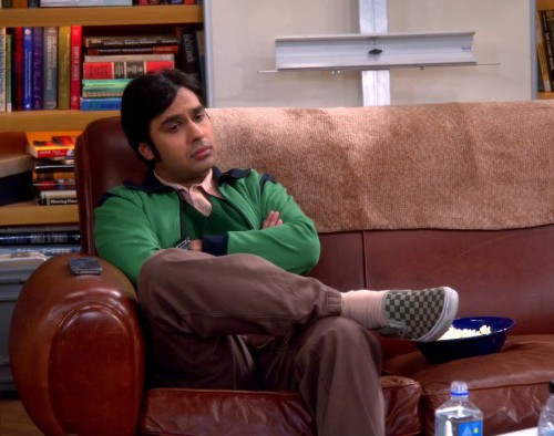 Still from American sitcom 'Big bang theory'. A brown Indian man in his late 20s, early 30s, sitting on a brown sofa with arms crossed, and one leg above the other, looking disconcerted.