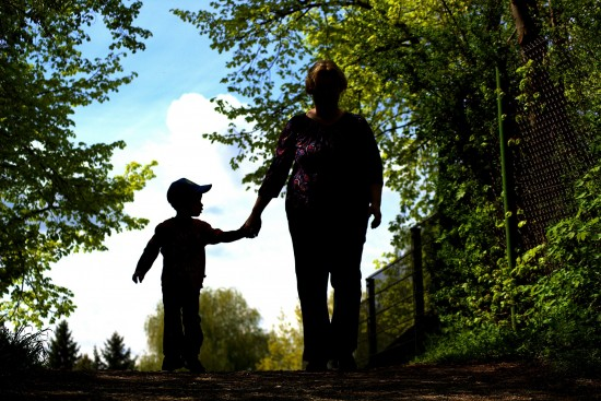 A woman walking, holding hands with her preschooler son in a garden.