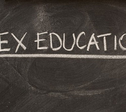 """""""Sex education"""" written with white chalk on a black board. It is in all caps and underlined."""