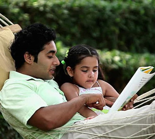A father with his little daughter on a hammock, reading together from a book.