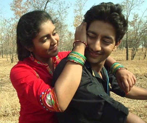 Still from film 'Sairat' (2016). A teenage girl sitting behind a teen boy on a two-wheeler. She has her arms on his shoulders, and is caressing his head with one hand. He is wearing a black shirt, and she is wearing a red ruit, green bangles, and a bindi on her forehead.