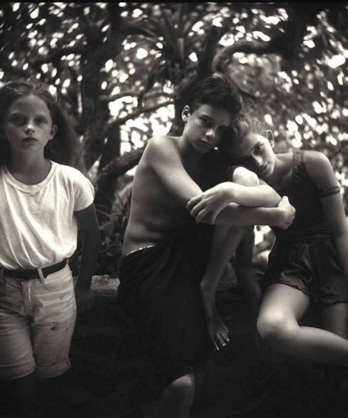 Black-and-white photo of three little children of about 5-7 years of age sitting on a branch of a tree. One girl is wearing knee-length shorts and tucked-in teeshirt; a boy wears a black knee-length shorts and and is naked above the waist; another girl resting her head on the boy's shoulder is wearing a thigh-length jumpsuit.
