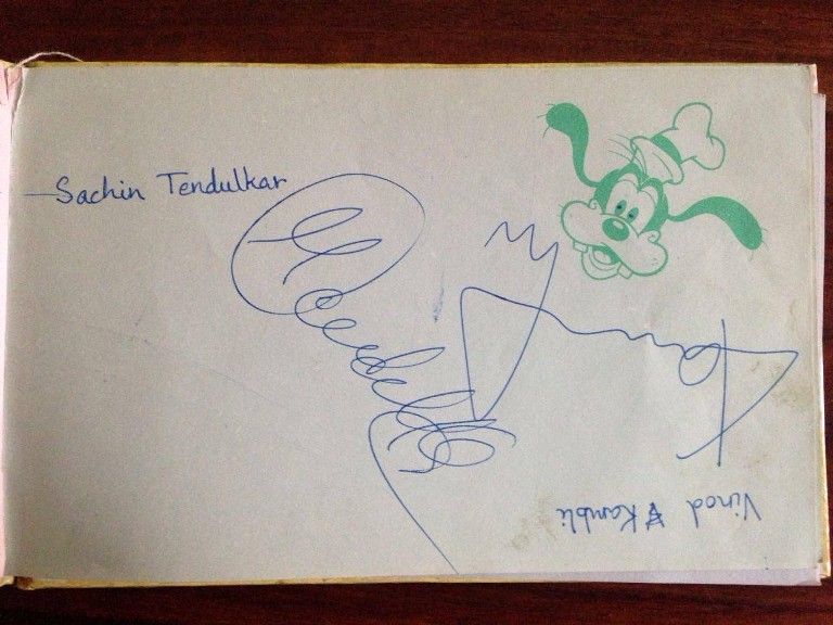Photo of a piece of paper from an autograph diary. It has signatures of Indian cricketers Vinod Kambli, and Sachin Tendlkar.