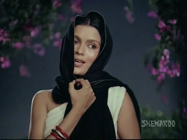 Still from a title song of Hindi film 'Satyam shivam sundaram'. A woman wearing light yellow-coloured saree with no blouse is clutching her dupatta that is covering her head. She is singing a song at night under a tree with small purple flowers.