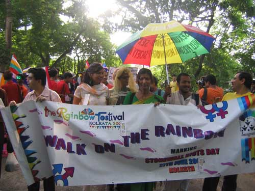 "Photo from an Indian LGTB festival. Several people carrying together a big placard that reads, ""The rainbow festival, Kolkata - Walk on the rainbow."" One of them also carry a rainbow-coloured umbrella. The sun shines above."