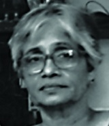 Black-and-white face-photo of Maya Sharma, middle-aged, white boy-cut hair, and is wearing specks.